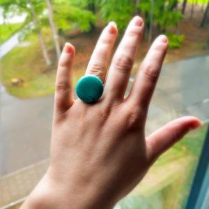 Ring met turquoise natuursteen. Verstelbare ring. Op de foto is de ring te zien om de ringvinger van een blanke vrouw, in de achtergrond is de natuur te zien.