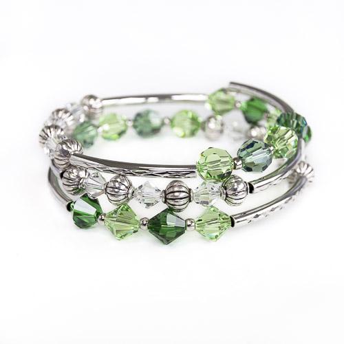 Armband met verschillende tintent groene (peridot) swarovski kralen, metalen kralen met een textuur, wit-half doorzichtige kralen en bewerkte metalen buisjes, geregen over een metalen memory-wire wikkel. die ongeveer 3 keer rond de pols gaat.