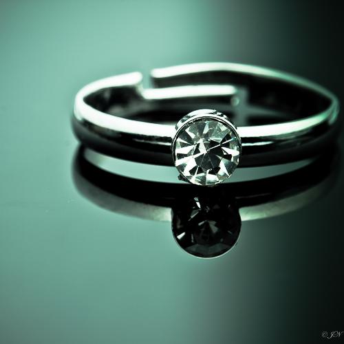 Metalen verstelbare ring met klein strass steentje in de kleur kristal (doorzichtig).