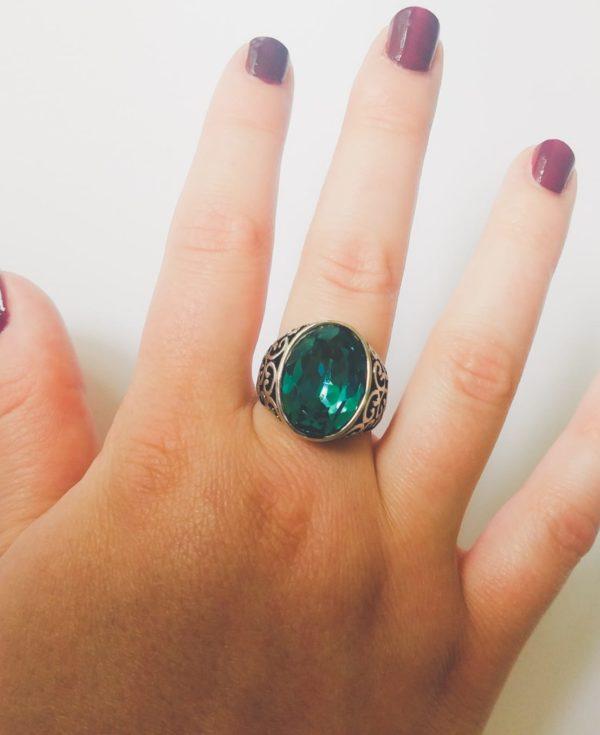 Gedecoreerde ring met een ovale swarovski fancy stone in de kleur indicolite (een blauw groene kleur). Op de foto is de ring te zien om de middelvinger van een blanke vrouw met bordeaux rode nagellak.