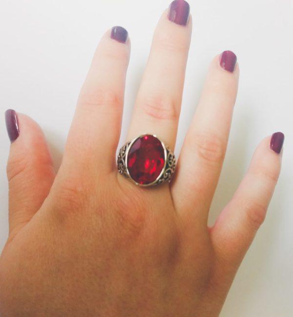 Gedecoreerde ring met een swarovski fancy stone in de kleur siam (rood). Op de foto is de ring te zien om de middelvinger van een blanke vrouw met bordeaux rode nagellak.