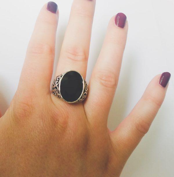 Gedecoreerde ring met een ovale swarovski fancy stone in de kleur jet (een zwarte kleur). Op de foto is de ring te zien om de vinger van een blanke vrouw met bordeaux rode nagellak.