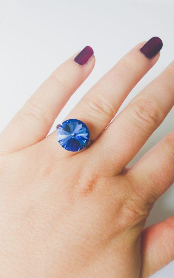 Ring met een ronde swarovski fancy stone in de kleur sapphire (donker blauw) gezet in een silver-plated verstelbare metalen ring. Op de foto is de ring te zien om de ringvinger van een blanke vrouw met bordeaux rode nagellak.