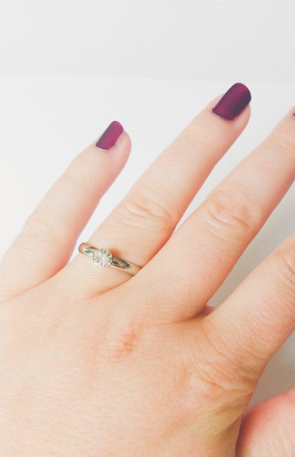Metalen verstelbare ring met klein strass steentje in de kleur kristal (doorzichtig). Op de foto is de ring te zien om de vinger van een blanke vrouw met bordeaux rode nagellak.