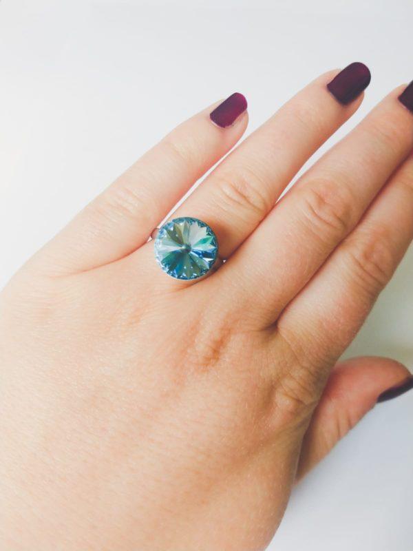 Ring met een ronde swarovski fancy stone in de kleur aquamarine (licht blauw) gezet in een silver-plated verstelbare metalen ring. Op de foto is de ring te zien om de ringvinger van een blanke vrouw met bordeaux rode nagellak.