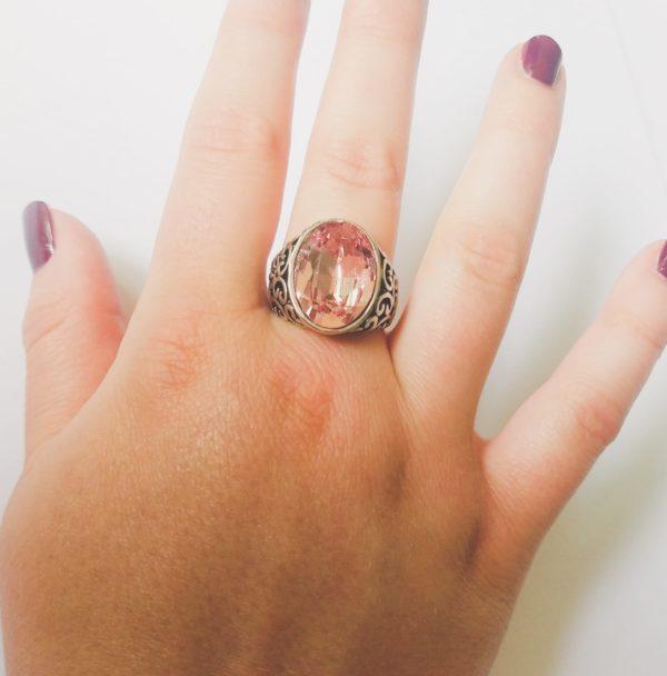 Gedecoreerde ring met een ovale swarovski fancy stone in de kleur light rose (een licht roze kleur). Op de foto is de ring te zien om de middelvinger van een blanke vrouw met bordeaux rode nagellak.