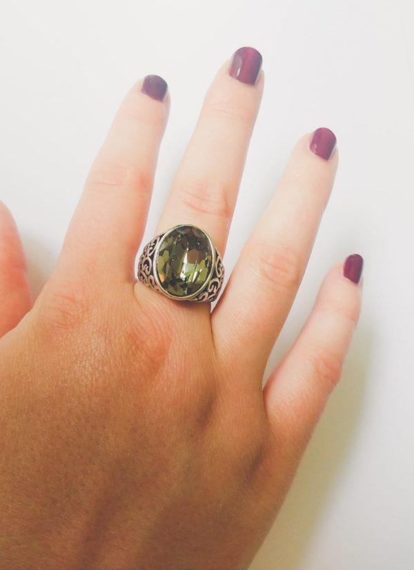 Gedecoreerde ring met een ovale swarovski fancy stone in de kleur crystal silver night (een grijze kleur). Op de foto is de ring te zien om de middelvinger van een blanke vrouw met bordeaux rode nagellak.