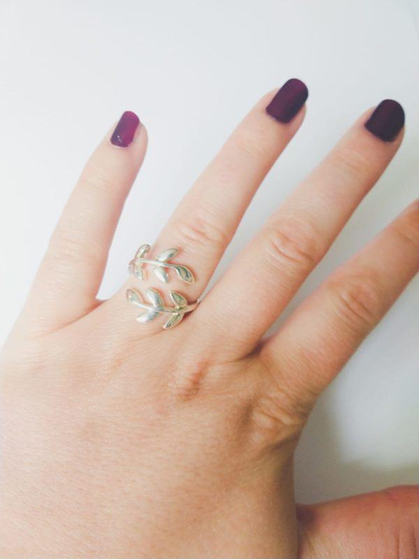 Silver-plated metalen ring met kleine blaadjes. De ring is verstelbaar. Op de foto is de ring te zien om de ringvinger van een blanke vrouw met bordeaux rode nagellak.
