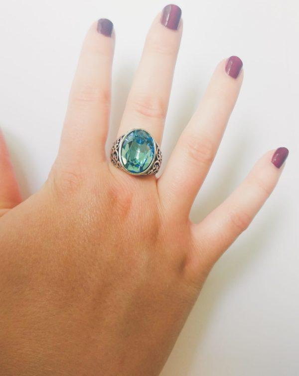Gedecoreerde ring met een ovale swarovski fancy stone in de kleur aquamarine (een licht blauwe kleur). Op de foto is de ring te zien om de middelvinger van een blanke vrouw met bordeaux rode nagellak.