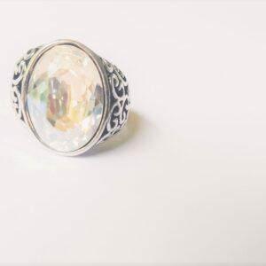 Ring met fijne decoratie met een ovale swarovski fancy stone in de kleur crystal moonlight. De ring wordt getoond op een witte achtergrond.