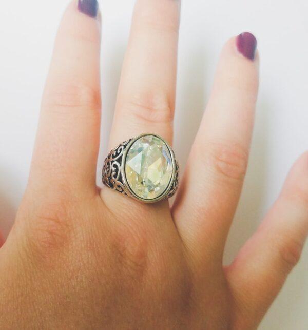 Ring met fijne decoratie met een ovale swarovski fancy stone in de kleur crystal moonlight. De ring wordt getoond om de middelvinger van een blanke vrouw met bordeaux rode nagellak, op een witte achtergrond.