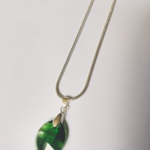 Silver plated ketting met een blad vormige swarovski hanger pure leaf in de kleur dark moss, donker groen, de hanger hangt aan een zilver kleurig klemmetje. De ketting wordt getoond op een witte achtergrond.