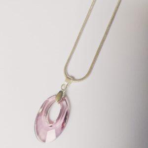 Silver plated ketting met ovaal vormige swarovski helios hanger in de kleur vintage rose een zacht roze kleur. De ketting wordt getoond op een witte achtergrond.