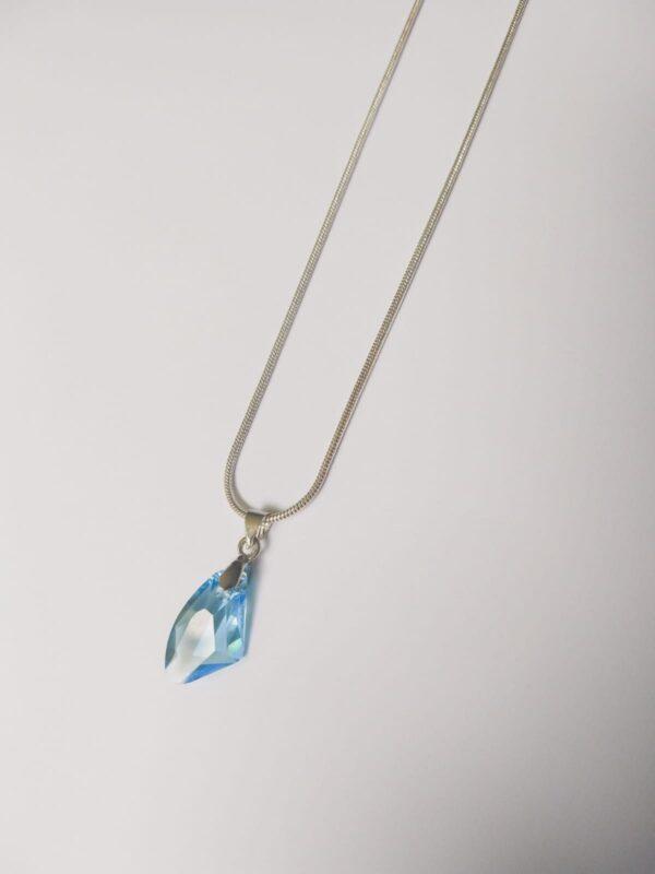 Silver-plated, korte ketting met aquamarine, licht blauwe assymetrische swarovski hanger. Deze ketting wordt getoont op een witte achtergrond.