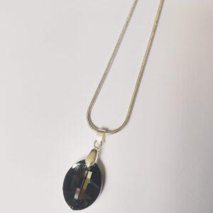 Silver plated ketting met een blad vormige swarovski hanger pure leaf in de kleur crystal silver night, grijs tot zilver, de hanger hangt aan een zilver kleurig klemmetje. De ketting wordt getoond op een witte achtergrond.