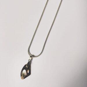 Silver-plated, korte ketting met crystal bronze shade, bruin assymetrische swarovski hanger. Deze ketting wordt getoont op een witte achtergrond.