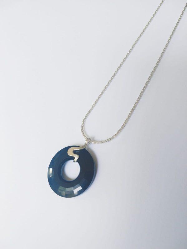 Silver plated ketting met een donut vormige swarovski disk in de kleur jet een diep zwarte kleur, de disk hangt aan een sierlijk 925 zilveren klemmetje. De ketting wordt getoond op een witte achtergrond.