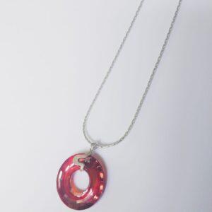 Silver plated ketting met een donut vormige swarovski disk in de kleur crystal red magma een donker rood tot donker oranje, de disk hangt aan een sierlijk 925 zilveren klemmetje. De ketting wordt getoond op een witte achtergrond.