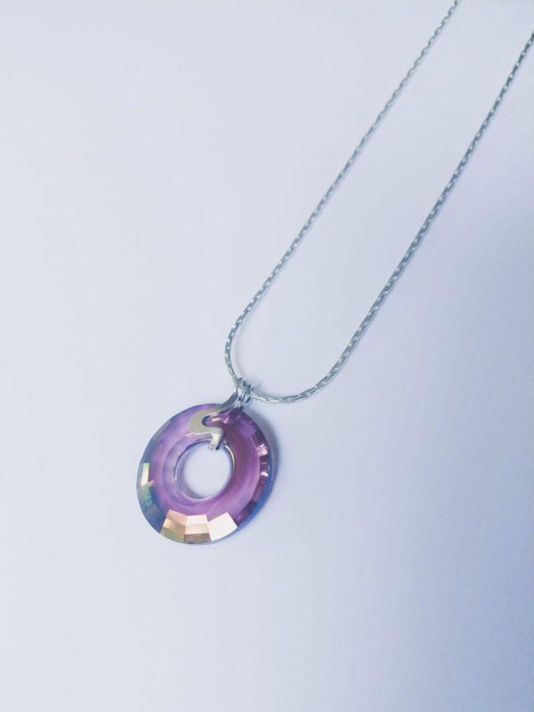 Silver plated ketting met een donut vormige swarovski disk in de kleur crystal lilac shadow, een paars tot goud, de disk hangt aan een sierlijk 925 zilveren klemmetje. De ketting wordt getoond op een witte achtergrond.