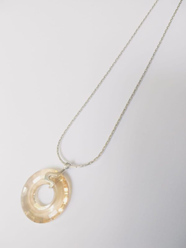 Silver plated ketting met een donut vormige swarovski disk in de kleur crystal golden shadow een licht bruin tot goud, de disk hangt aan een sierlijk 925 zilveren klemmetje.. De ketting wordt getoond op een witte achtergrond.
