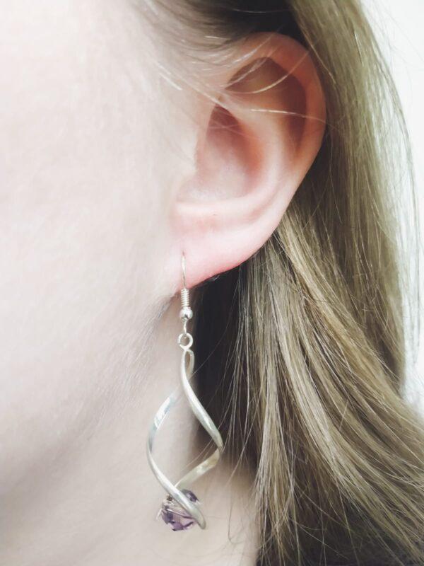 Oorbel wikkel met swarovski kraal in de kleur antique pink, een oud roze/paarse kleur. De oorbel wordt getoond in het oor van een blanke vrouw met blond haar.