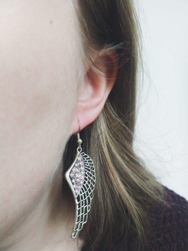 Oorbelen met een wing (vleugelvormige hanger) met swarovski steentjes in de kleur crystal silver night, grijze kleur. Op de foto is een de oorbel in het oor van een blanke vrouw met blond haar.
