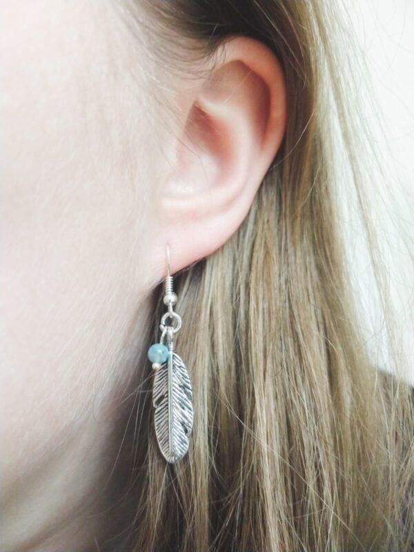 Oorbellen feather turquoise. Een metalen veer hanger met een turquoise kraaltje. De oorbel wordt getoond in het oor van een blanke vrouw met blond haar.