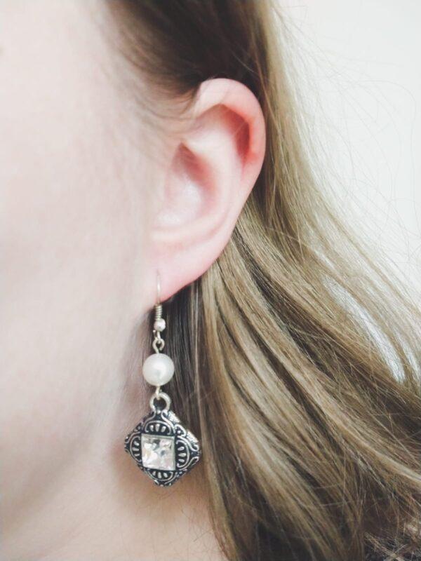 Metalen gedecoreerde hanger met een vierkante swarovski steen in de kleur crystal, met een swarovski parel in de kleur white (wit). De oorbel wordt getoond in het oor van een blanke vrouw met blond haar.