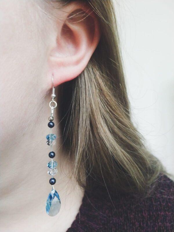 Lange oorbellen met een druppelvormige swarovski hanger in de kleur aquamarine (licht blauw) met daarboven swarovski kralen in de kleur aquamarine (licht blauw) en crystal, en parels in night blue, een donker blauwe kleur. De oorbel wordt getoond in het oor van een blanke vrouw met blond haar.