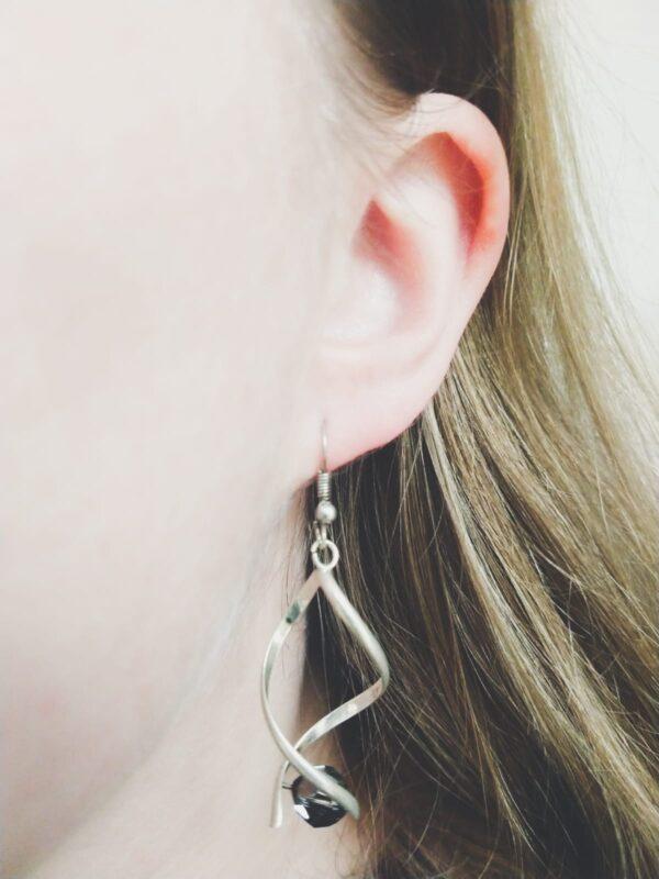 Oorbellen met silver-plated wikkel met een swarovski kraal in de kleur jet hematite, een zwarte kleur. De oorbel wordt getoond in het oor van een blanke vrouw met blond haar.