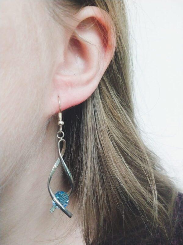 Oorbellen met silver-plated wikkel met een swarovski kraal in de kleur aquamarine, een licht blauwe kleur. De oorbel wordt getoond in het oor van een blanke vrouw met blond haar.