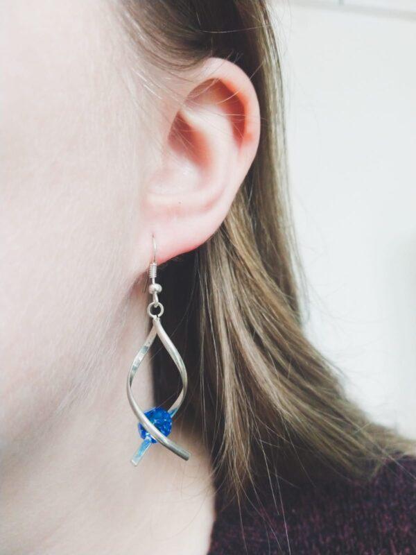 Oorbellen met silver-plated wikkel met een swarovski kraal in de kleur capri blue, een blauwe kleur. De oorbel wordt getoond in het oor van een blanke vrouw met blond haar.