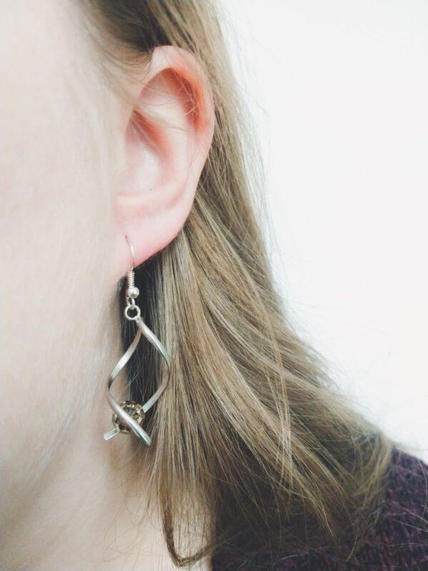 Oorbellen met silver-plated wikkel met een swarovski kraal in de kleur crystal bronze shade, een bruine kleur. De oorbel wordt getoond in het oor van een blanke vrouw met blond haar.