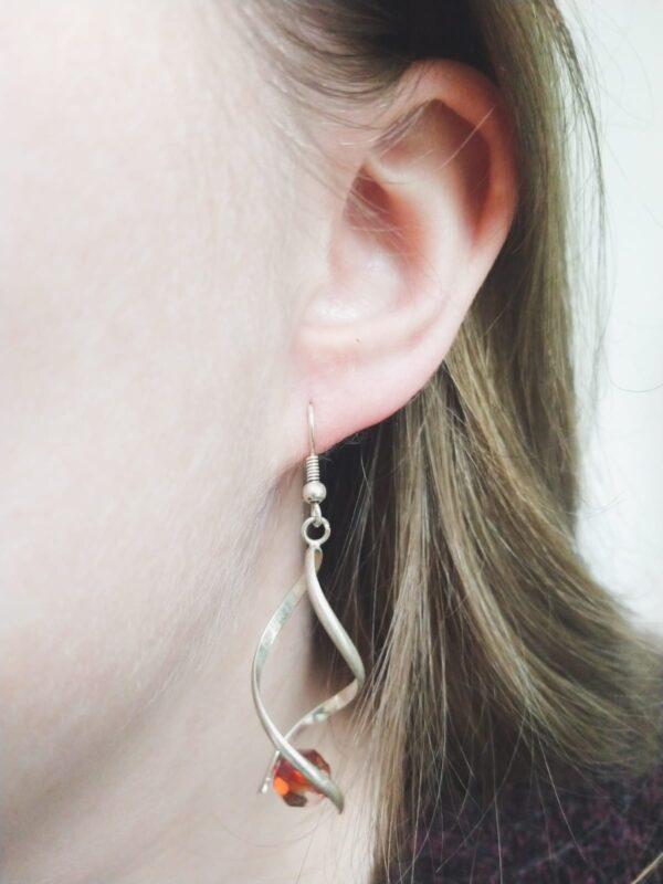 Oorbellen met silver-plated wikkel met een swarovski kraal in de kleur crystal red magma, een rode/oranje kleur. De oorbel wordt getoond in het oor van een blanke vrouw met blond haar.