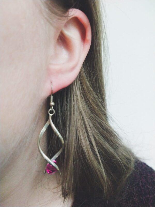 Oorbellen met silver-plated wikkel met een swarovski kraal in de kleur fushia, een donker roze kleur. De oorbel wordt getoond in het oor van een blanke vrouw met blond haar.
