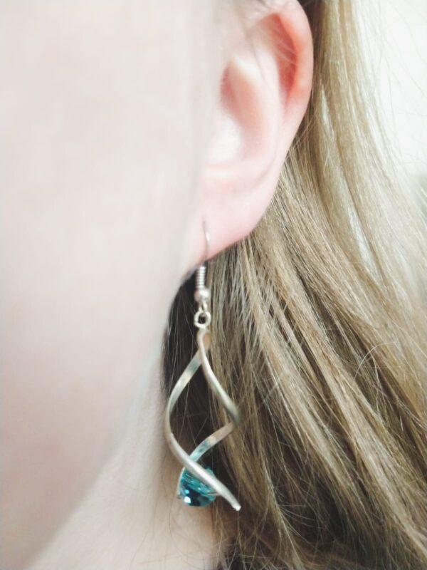 Oorbellen met silver-plated wikkel met een swarovski kraal in de kleur indicolite, een blauw/groene kleur. De oorbel wordt getoond in het oor van een blanke vrouw met blond haar.