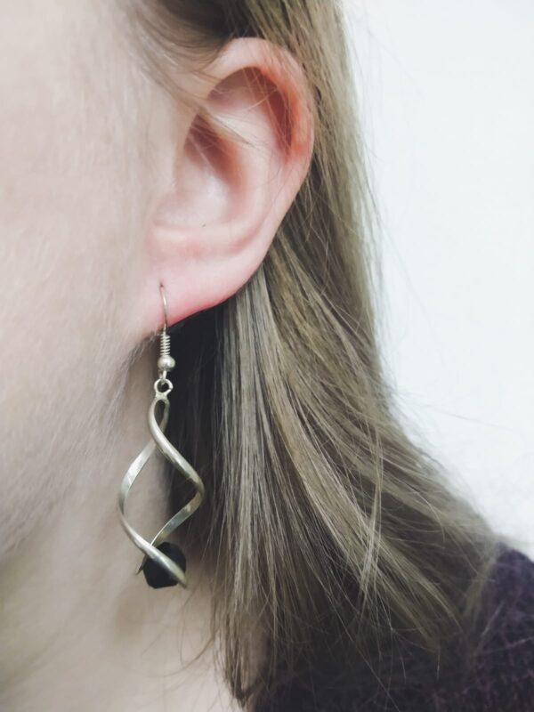 Oorbellen met silver-plated wikkel met een swarovski kraal in de kleur jet, een zwarte kleur. De oorbel wordt getoond in het oor van een blanke vrouw met blond haar.