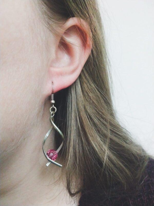 Oorbellen met silver-plated wikkel met een swarovski kraal in de kleur rose, een roze kleur. De oorbel wordt getoond in het oor van een blanke vrouw met blond haar.