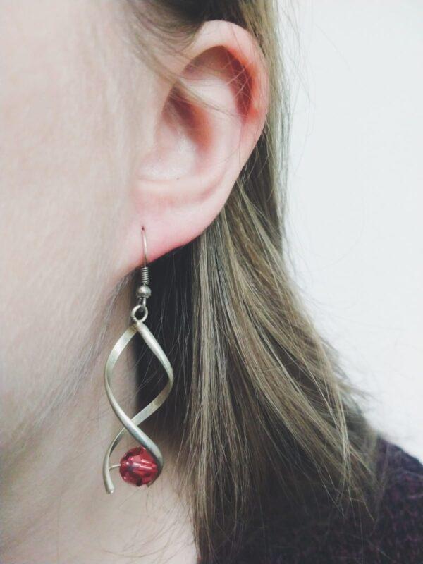 Oorbellen met metalen wikkel met een swarovski kraal in de kleur padparadscha, een roze/oranje kleur. De oorbel wordt getoond in het oor van een blanke vrouw met blond haar.