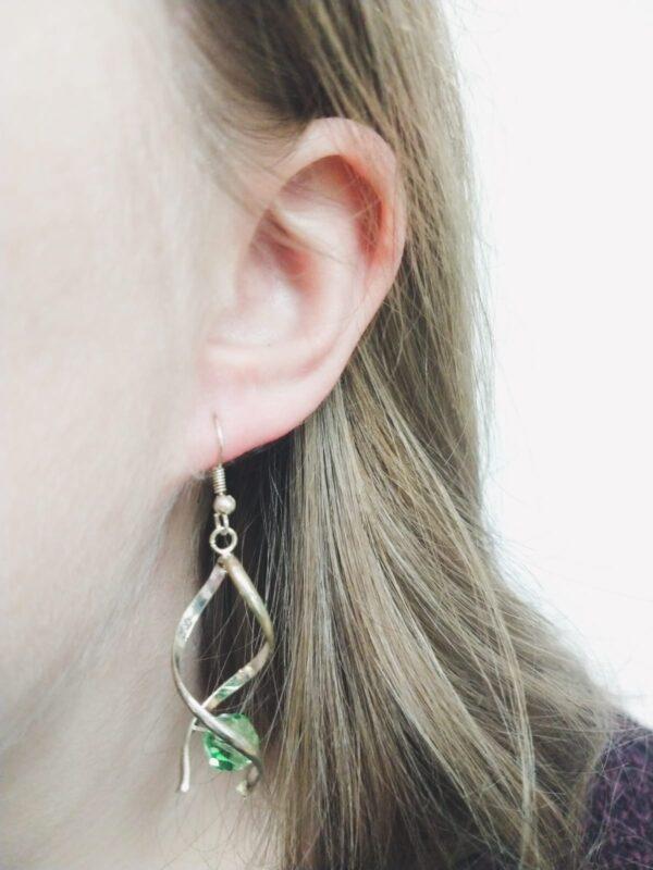 Oorbellen met silver-plated wikkel met een swarovski kraal in de kleur peridot, een licht groene kleur. De oorbel wordt getoond in het oor van een blanke vrouw met blond haar.
