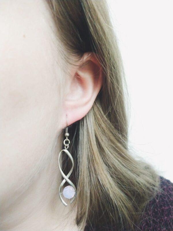 Oorbellen met silver-plated wikkel met een swarovski kraal in de kleur rose water opal, een licht roze kleur. De oorbel wordt getoond in het oor van een blanke vrouw met blond haar.