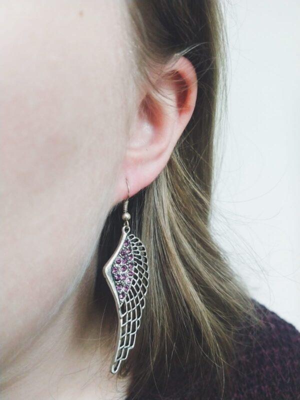 Oorbellen met een wing (vleugelvormige hanger) met swarovski steentjes in de kleur amethyst, een donker paarse kleur. De oorbel wordt getoond in het oor van een blanke vrouw met blond haar.