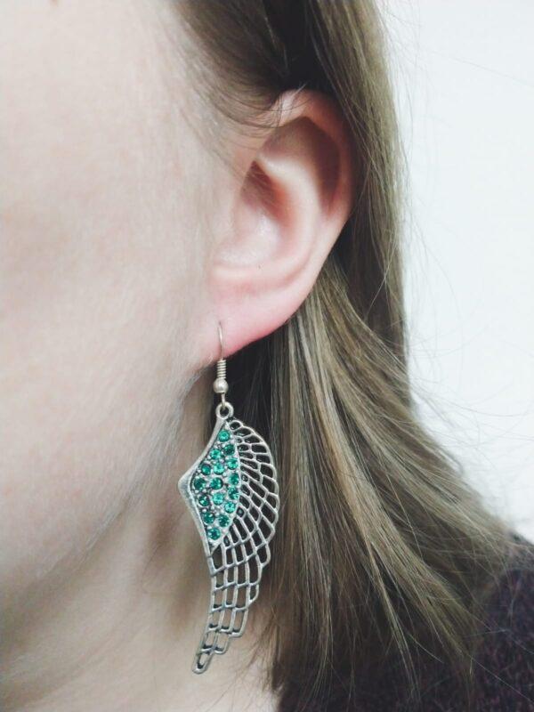 Oorbellen met een wing (vleugelvormige hanger) met swarovski steentjes in de kleur emerald, een donker groene kleur. De oorbel wordt getoond in het oor van een blanke vrouw met blond haar.
