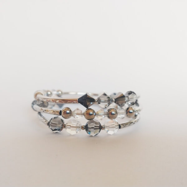 Armband met verschillende tinten grijs (crystal silver night) swarovski kralen, metalen kralen, wit-half doorzichtige kralen en bewerkte metalen buisjes, geregen over een metalen memory-wire wikkel. die ongeveer 3 keer rond de pols gaat.