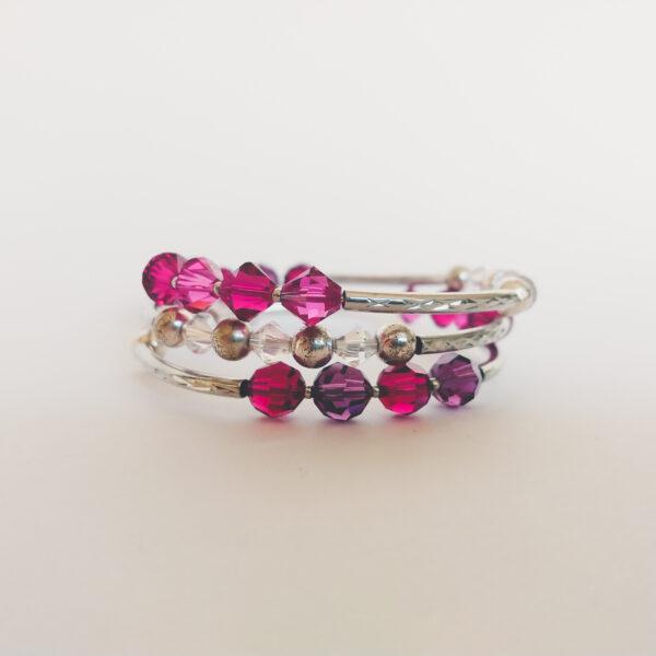 Armband met verschillende tinten roze en paars (fuchsia) swarovski kralen, metalen kralen, wit-half doorzichtige kralen en bewerkte metalen buisjes, geregen over een metalen memory-wire wikkel. die ongeveer 3 keer rond de pols gaat.