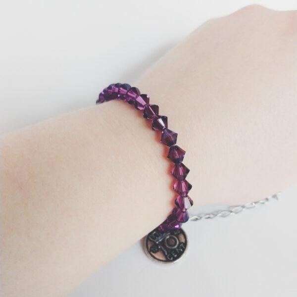 Armband swarovski xilion 6 mm donker paars. Een armband met kleine 6 mm hoekige kraaltjes in amethyst (een donker paarse kleur). De armband wordt getoond om de pols van een blanke vrouw.