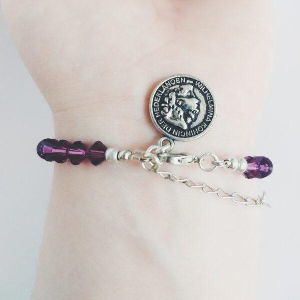 Armband swarovski xilion 6 mm donker paars. Een armband met kleine 6 mm hoekige kraaltjes in amethyst (een donker paars kleur). Met een metalen bedeltje in de vorm van een muntje. De onderkant van de armband wordt getoond om de pols van een blanke vrouw.