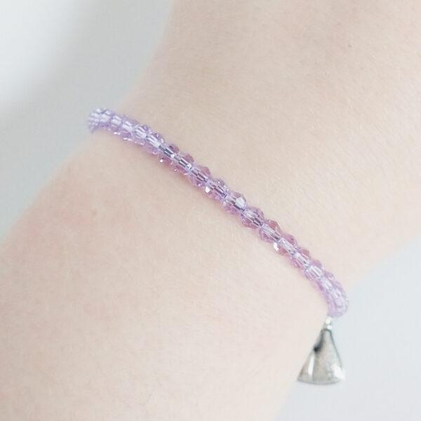 Een armband met kleine 4 mm ronde kraaltjes in lilac (een licht paarse kleur). De armband wordt getoond om de pols van een blanke vrouw.