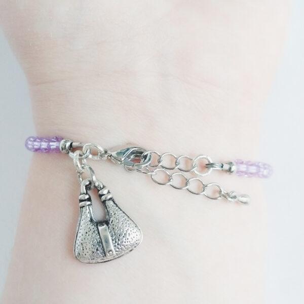 Een armband met kleine 4 mm ronde kraaltjes in lilac (licht paarse kleur). Met een metalen bedeltje in de vorm van een tasje. De onderkant van de armband wordt getoond om de pols van een blanke vrouw.
