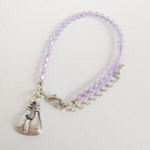 Een armband met kleine 4 mm ronde kraaltjes in lilac (een licht paarse kleur). Met een metalen bedeltje in de vorm van een tasje.